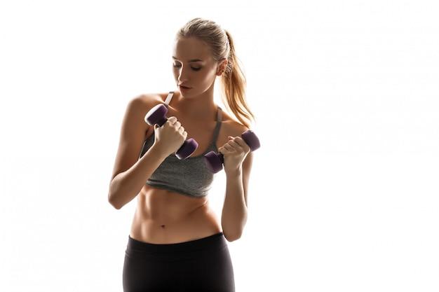 Piękny sportowy kobieta szkolenia z hantlami