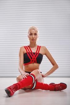 Piękny sportowy młody żeński rozciąganie przed jej treningiem