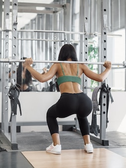 Piękny sportowy sexy kobieta robi przysiady trening w siłowni