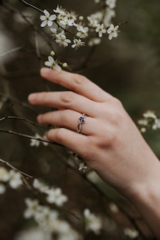 Piękny srebrny pierścionek z fioletowym diamentem na miękkiej kobiecej dłoni