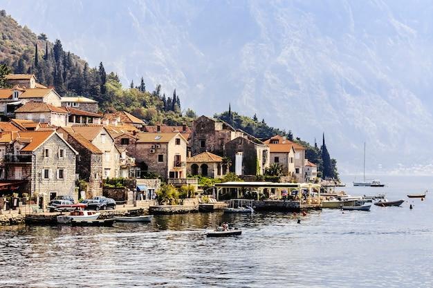 Piękny śródziemnomorski krajobraz - średniowieczne miasto na linii plaży na tle gór, zatoka kotorska, czarnogóra