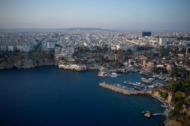 Piękny śródziemnomorski krajobraz w turcji. panoramiczny widok na wybrzeże morskie z zabudowaniami na brzegu. łodzie i jachty zakotwiczone w porcie w zatoce morskiej.