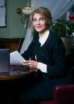 Piękny starszy bizneswoman pracuje w kawiarni z laptopem i notepad