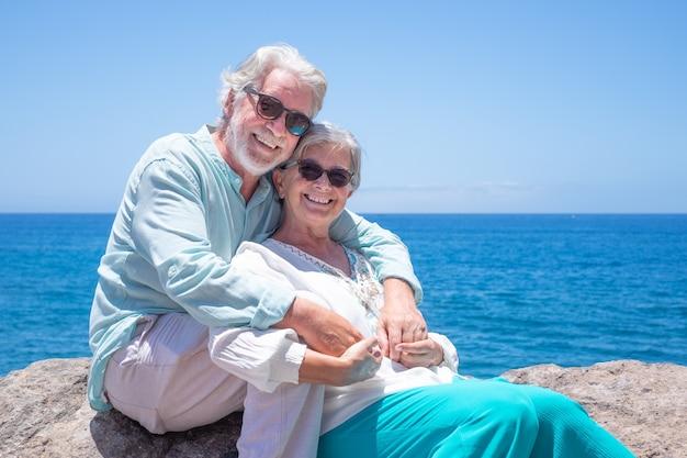 Piękny starszy para emeryt korzystających z wakacji na morzu, siedząc i objął, patrząc na kamery. niebieski horyzont nad wodą