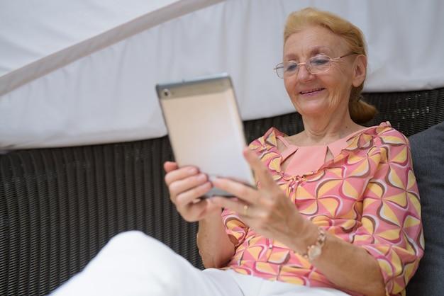 Piękny starszy turysta kobieta o blond włosach relaksujący wokół