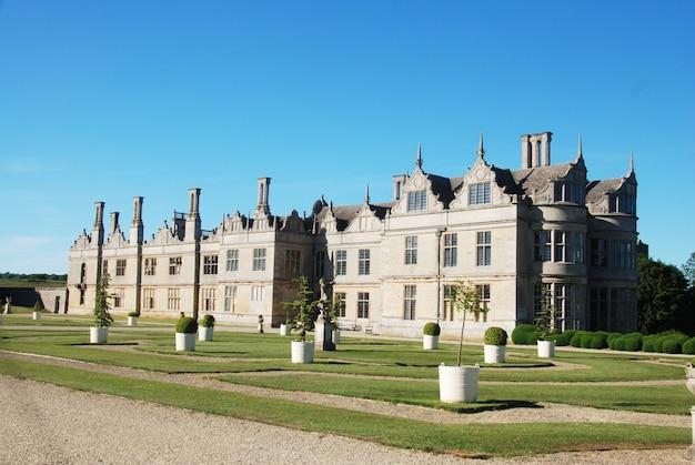 Piękny stary angielski zamek z zielonym ogrodem, błękitne niebo.