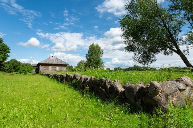 Piękny stary drewniany dom z kamiennym ogrodzeniem w malowniczej okolicy.