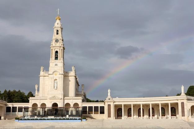 Piękny stary kościół w fatimie na tle nieba, a na nim tęcza
