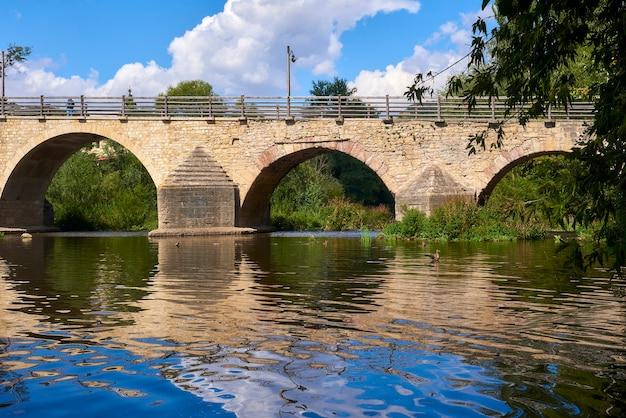 Piękny stary most nad spokojną rzeką w słoneczny dzień