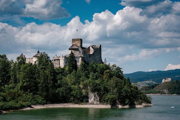 Piękny stary zamek na skale nad rzeką w krajobrazie polski