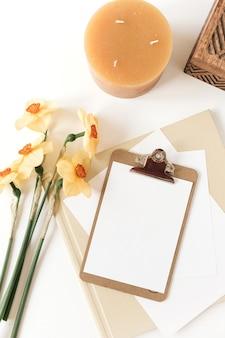 Piękny stół biurowy w domu biurko ze świeżymi kwiatami narcyza, drewnianą trumną, świecą, albumami