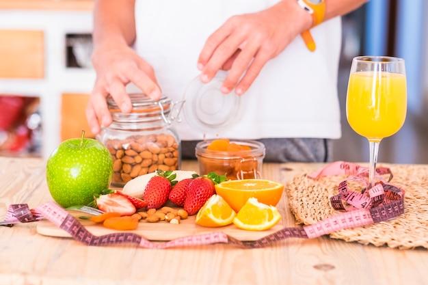 Piękny stół pełen jedzenia takich jak owoce, aby zjeść dobre i smaczne śniadanie w domu, aby schudnąć i pozostać przy sobie - w stole są banany, borówki, pomarańcze, jabłka i inne