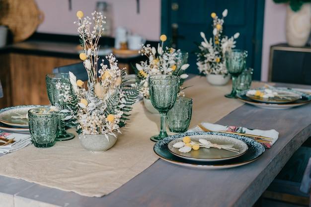 Piękny stół wykonany z talerzy, szklanek i kwiatów.