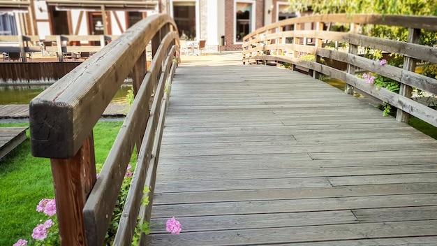 Piękny stonowany obraz małego drewnianego mostu przez rzekę w europejskim mieście w jasny słoneczny dzień