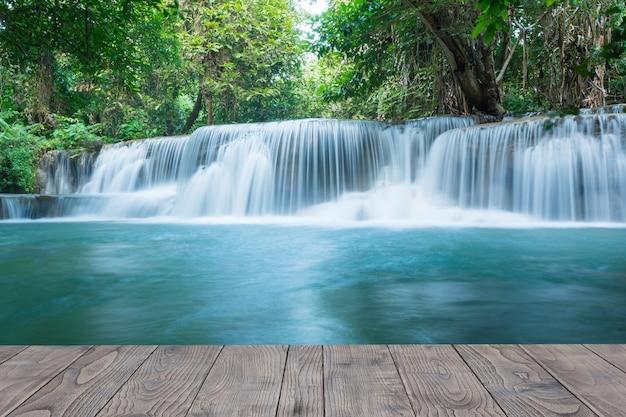 Piękny strumień wodospadu w lesie deszczowym z drewnianym biurkiem