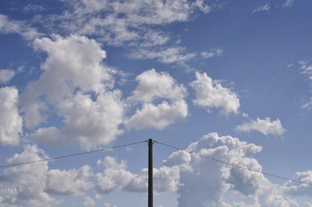 Piękny strzał białe chmury na niebieskim niebie z słupem prądu w środku