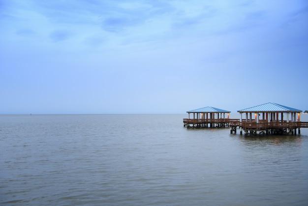 Piękny strzał drewniany molo na morzu pod chmurnym niebem