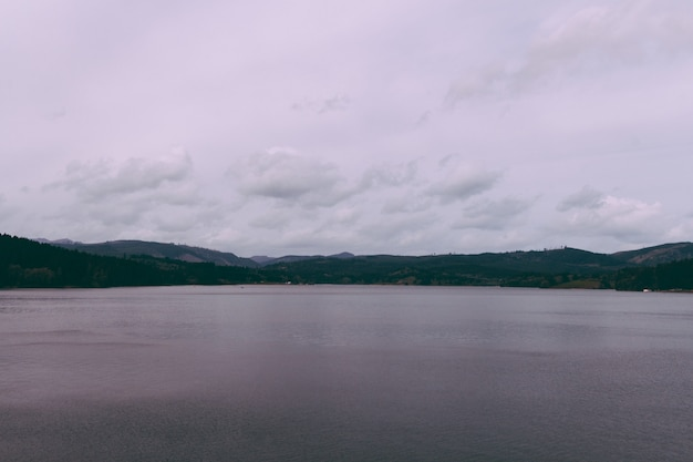 Piękny strzał jezioro z wzgórzami na horyzoncie i chmurnym niebem