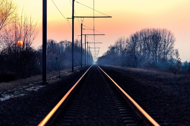 Piękny strzał linia kolejowa na wsi z zadziwiającym różowym niebem przy świtem