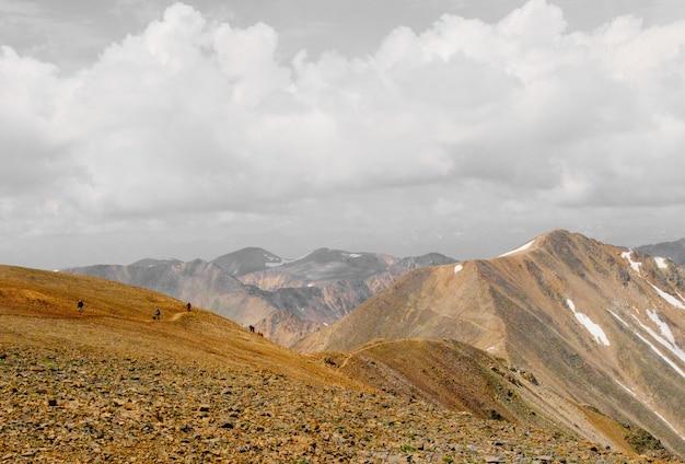 Piękny strzał ludzie chodzi w górę góry w odległości pod chmurnym niebem