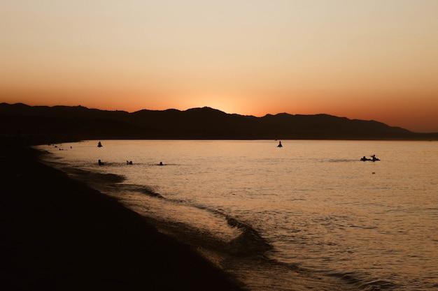 Piękny strzał ludzie pływa w wodzie blisko brzeg z jasnym niebem