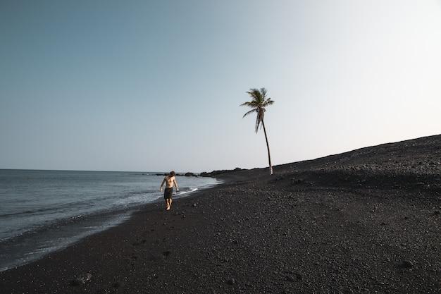Piękny strzał męski jest ubranym swimsuit odprowadzenie na piaskowatym seashore blisko drzewka palmowego