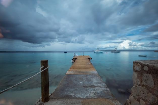 Piękny strzał molo prowadzi ocean pod ponurym niebem w bonaire, karaiby