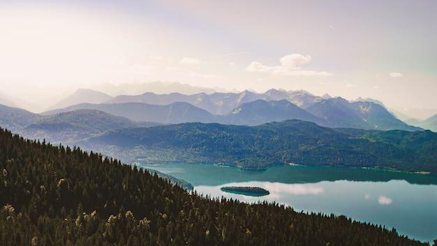 Piękny strzał na dużej wysokości jezioro otoczone zielonymi górami z niebem