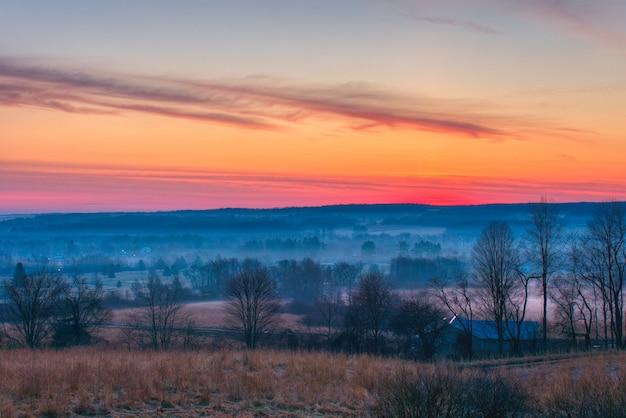 Piękny strzał niesamowitych czerwonych i pomarańczowych chmur nad dużymi mglistymi polami i lasem o świcie