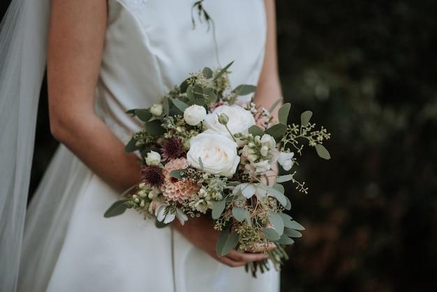 Piękny strzał panna młoda jest ubranym ślubną suknię trzyma kwiatu bukiet