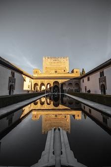 Piękny strzał pionowy wielkiego pałacu w hiszpanii z odbiciem w basenie