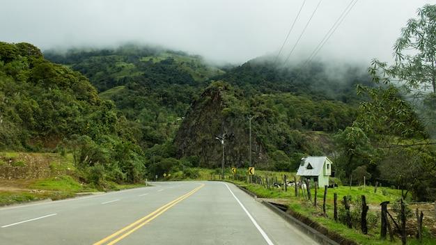 Piękny strzał pustej zakrzywionej drogi na wsi z niesamowitymi chmurami podczas mglistego dnia