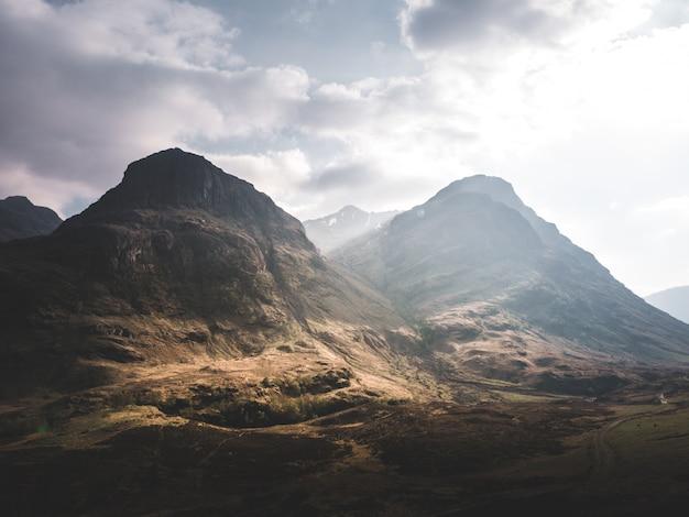 Piękny strzał skalistych stromych gór i wzgórz pod zapierającym dech w piersiach pochmurnym niebem