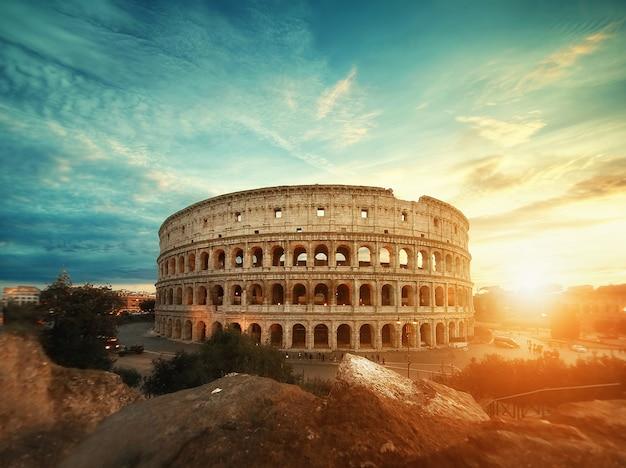 Piękny strzał słynnego rzymskiego amfiteatru w koloseum pod zapierającym dech w piersiach niebem o wschodzie słońca