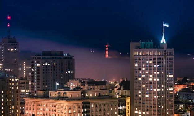 Piękny strzał w centrum san fransisco budynku z mostem golden gate w nocy