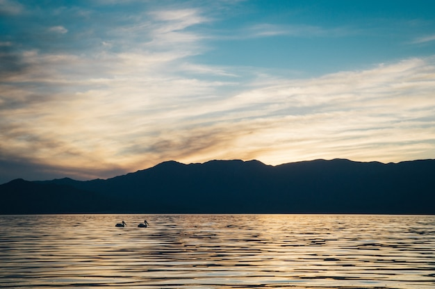 Piękny strzał w morze z ciemnymi wzgórzami i niesamowitym niebem o zachodzie słońca
