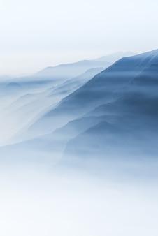 Piękny strzał wysokie białe szczyty i góry pokryte mgłą