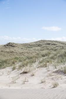 Piękny strzał wzgórza pokryte trawą pod jasnym błękitnym niebem