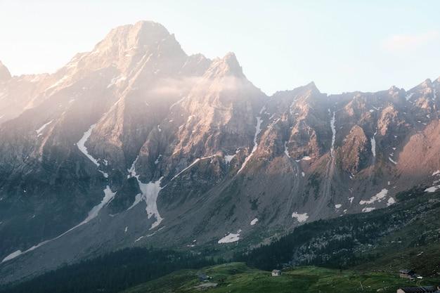 Piękny strzał z domu na trawiastym wzgórzu z górami i jasnym niebem