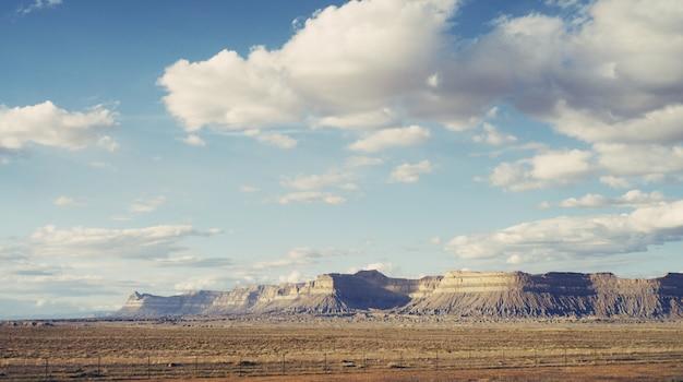 Piękny strzał z dużej pustyni z zapierającymi dech w piersiach chmurami i skalistymi wzgórzami
