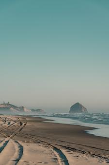 Piękny strzał z piaszczystej plaży z niesamowitymi falami w słoneczny dzień
