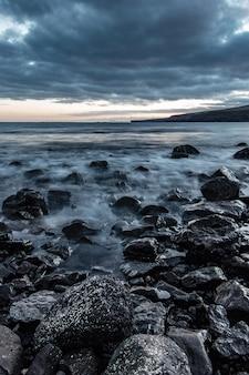 Piękny strzał z skalistego wybrzeża morskiego z niesamowitą teksturą wody i zapierającym dech w piersiach pochmurnym szarym niebem