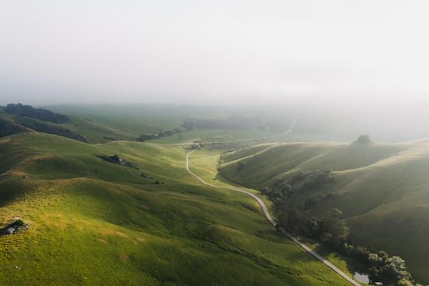 Piękny strzał zieleni wzgórza pod jasnym niebieskim niebem