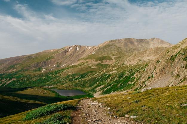 Piękny strzał zieleni wzgórza zbliża góry z stawem w odległości pod chmurnym niebem