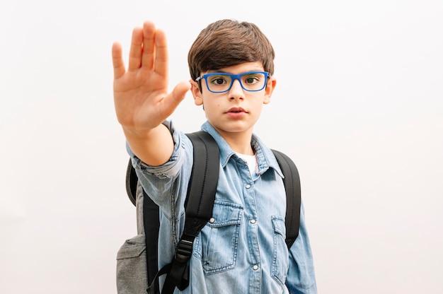 Piękny student chłopiec dziecko nosi plecak trzymając książki na białym tle z otwartą ręką robi znak stopu