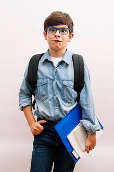 Piękny student chłopiec dziecko nosi plecak trzymając książki na na białym tle