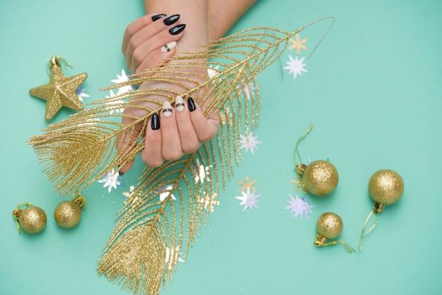 Piękny stylowy żeński manicure na miętowej powierzchni