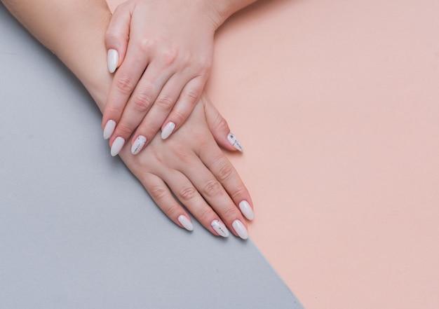Piękny stylowy żeński manicure na różowym tle.