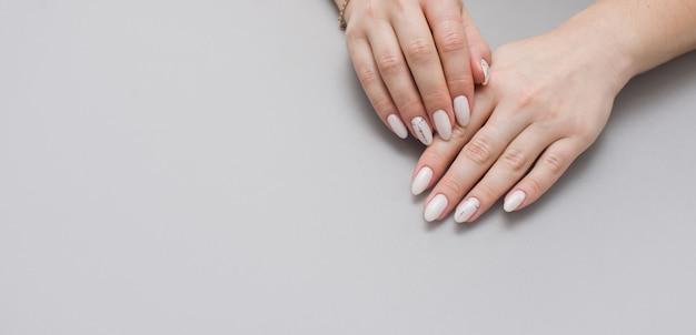 Piękny stylowy żeński manicure na szarym tle.