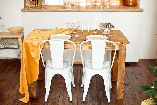 Piękny świątecznie urządzony pokój w stylu skandynawskim, świąteczny stół ze stołem i choinka z prezentami pod nim